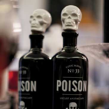 Black and White detail of 'poison' bottles with white ceramic skull toppers for a scary Halloween dinner party, Boston Event Planner, Boston Event Planning, Boston Event Stylist, Boston Event Styling