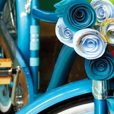 Blue detail of quilled flowers decorating an old-fashioned bicycle for a travel-themed corporate celebration, Boston Event Planner, Boston Event Planning, Boston Event Stylist, Boston Event Styling